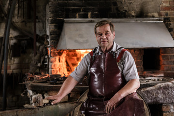 Portrait of blacksmith in his workshop front of the fire