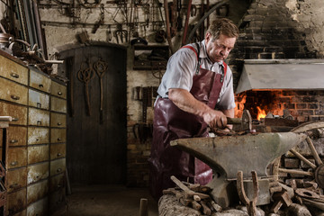 Blacksmith hammering on red hot pick laying on anvil
