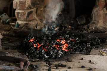 Fire burning down in furnace of a blacksmiths workshop