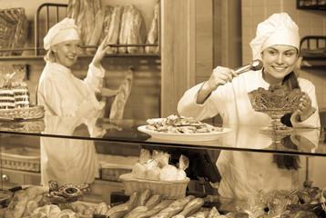 Keuken foto achterwand Bakkerij Smiling women selling fresh pastry and loaves