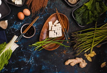 Tofu cheese and Fresh ingredients ready to prepare asian dinner meal. Diet, vegan, and detox food concept.