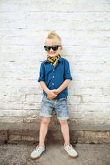 стильный мальчик в солнцезащитных очках возле кирпичной белой стены