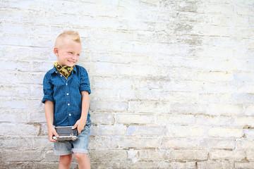 мальчик блондин с фотоаппаратом возле белой кирпичной стены