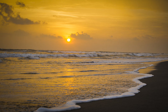 Sunset on the beach with waves crashing