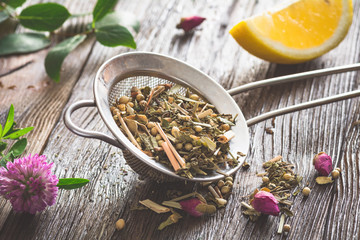 Dry herbal tea with clover, rose buds and lemon. Toned image, horizontal