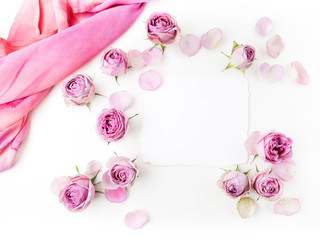Framework from roses and silk on white background. Flat lay. Top view