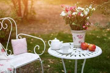 White porcelain set for tea or coffee on table in the garden over blur green nature background.