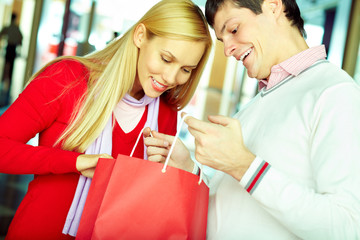 Young woman looking what her boyfriend have bought for her