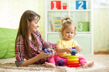Mother and kid with toys in playroom