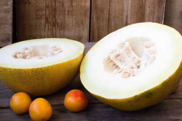 Sliced melon with ripe apricots on rustic wooden background, fro