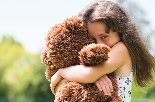 Girl embracing teddy bear