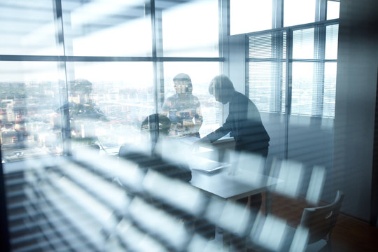 Business people in office, viewed through jalousie