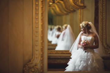 Charming bride next to the luxury mirror