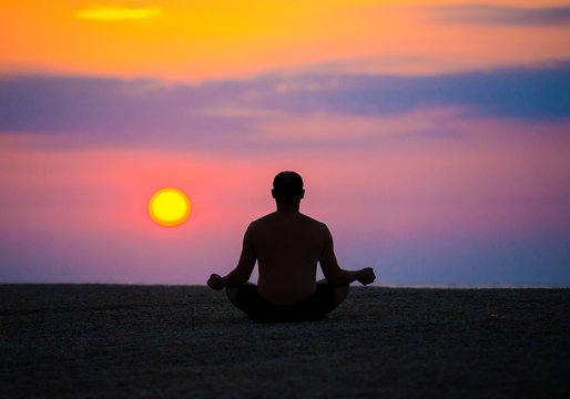 man practices yoga on the beach, the sea.