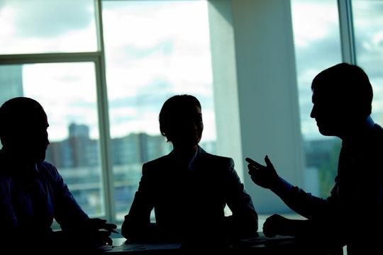 Three business people talking in dark office