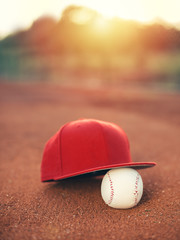Baseball cap and ball at sunset