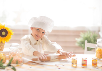 little boy in the form of a cook rolls out the dough