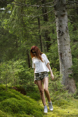 beautiful woman enjoying nature in forest green mountains