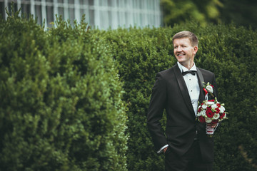 groom waiting for his wife in a green garden
