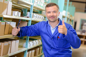 Man in warehouse holding up thumb