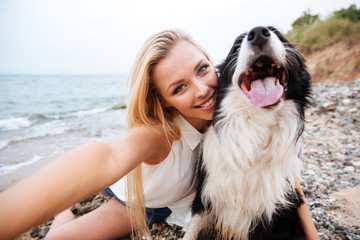 Happy woman sitting and making selfie with dog on beach