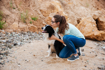 Happy charming young woman sitting and hugging her dog