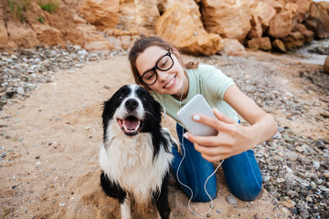 Girl in eyeglasses taking selfie with her dog on smartphone