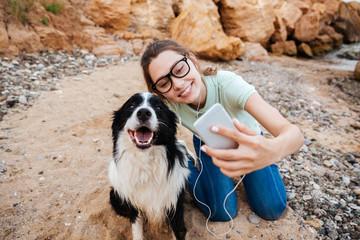Girl in eyeglasses taking selfie with her dog on smartphone