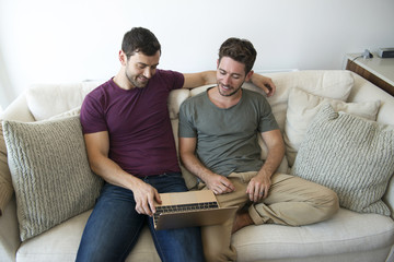Gay Male Couple Sitting On Sofa At Home Using Laptop