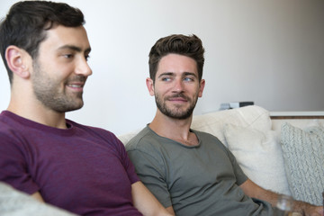 Gay Male Couple Relax On Sofa