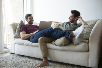 Gay Male Couple Relax On Sofa Watching TV And Using Laptop