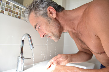 Mature man in bathroom washing his face in sink