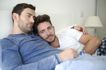 Portrait Of Gay Male Couple At Home Relaxing In Bed Together