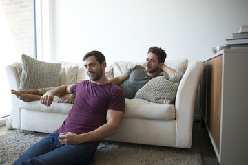 Gay Male Couple Relax On Sofa Watching TV