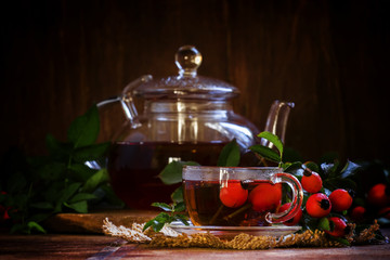 Healing black tea with wild rose berries in a glass cup. Vintage