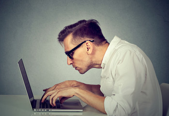 young man in glasses working on computer sitting at desk