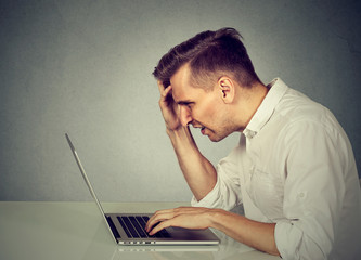 Side profile stressed man working on laptop sitting at table