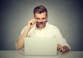 Confused shocked man looking at his laptop
