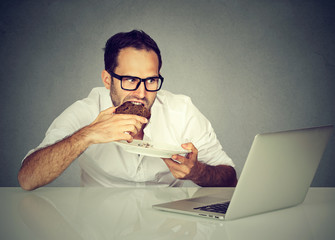 Young student man eating while working on laptop