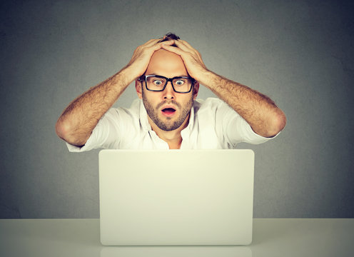 Stressed man looking at his laptop computer