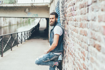Knee figure of young beautiful caucasian bearded tattooed man leaning against a brick wall, overlooking pensive - fashion, thoughtful, thinking future concept