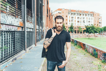 Knee figure of young beautiful caucasian bearded tattooed man posing looking at camera, holding leather jacket - pensive, fashion, beauty concept