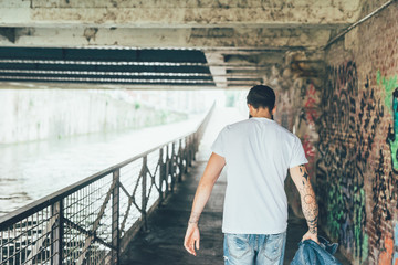 From behind knee figure view of young beautiful caucasian bearded tattooed man strolling through the street of a city