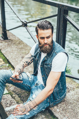 young beautiful caucasian bearded tattooed man sitting on the floor outdoor in the city, holding smart phone, overlooking - technology, pensive, thinking future concept