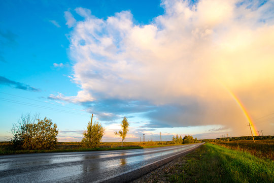 Landscape with country road and rainbow