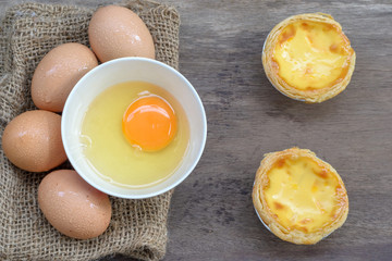 Egg tart custard sweet delicious dessert with fresh eggs on wood background