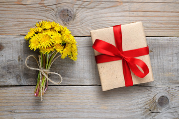 Dandelion flowers and gift box on wooden background