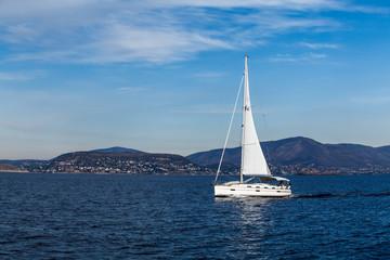 Rejs jachtem po morzu w błękitach nieba i pięknym słońcu