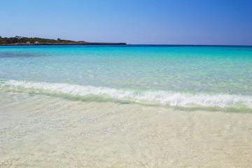 Clear water and white sand at Cala Son Saura beach, Menorca.