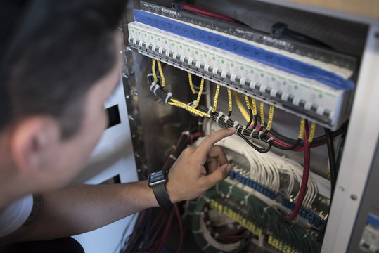 Young electrician repairing boat control